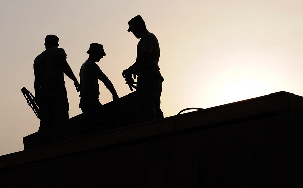 A silhouette of three workers