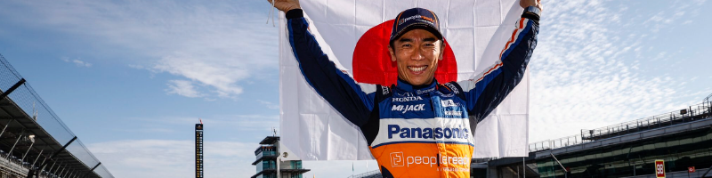 Takuma Sato standing in a victory pose at the Indy 500